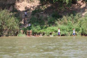 Eindrücke auf der Fahrt - im Mekong spielende Kinder in der Nähe von Pakse